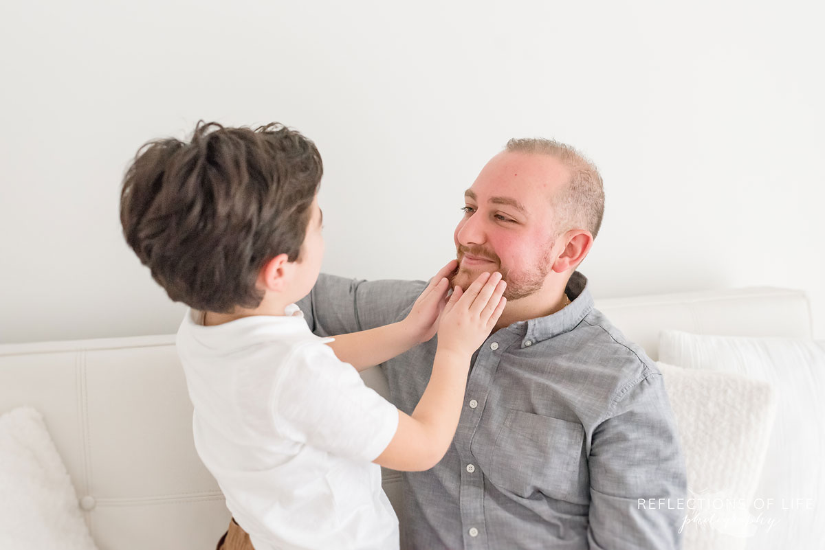 little boy holding dads face