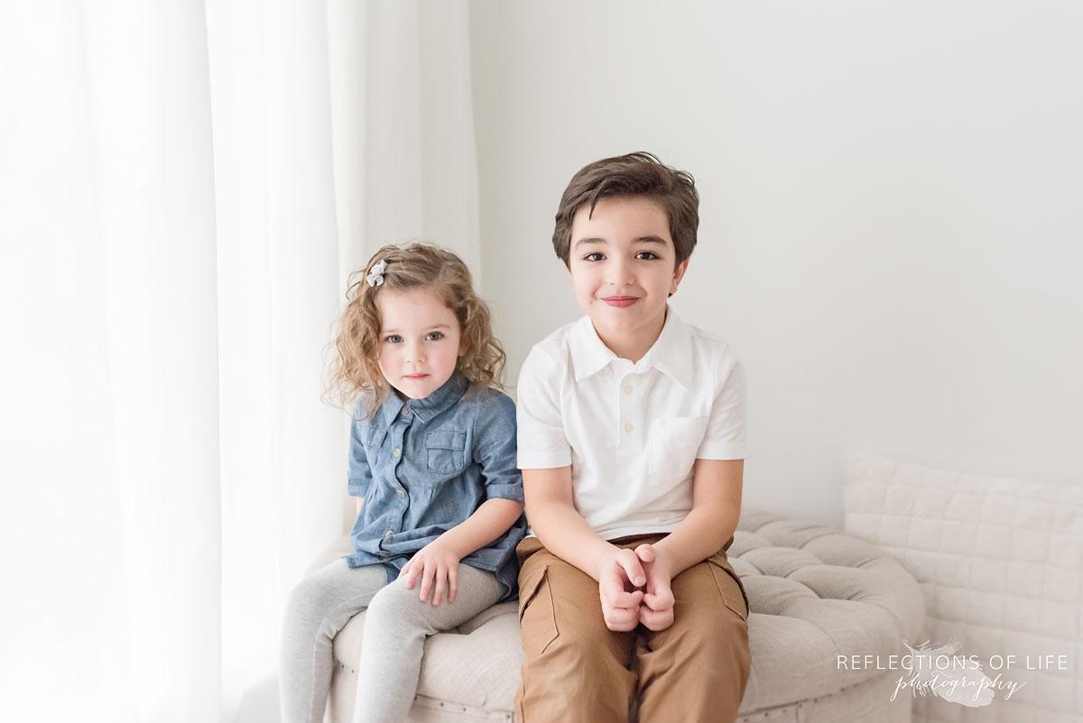 siblings in white studio