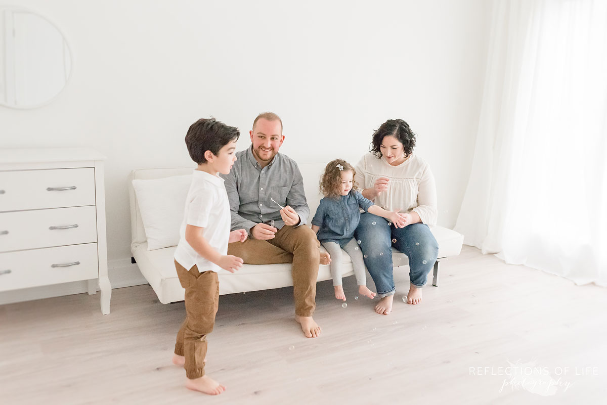 family blowing bubbles in white studio