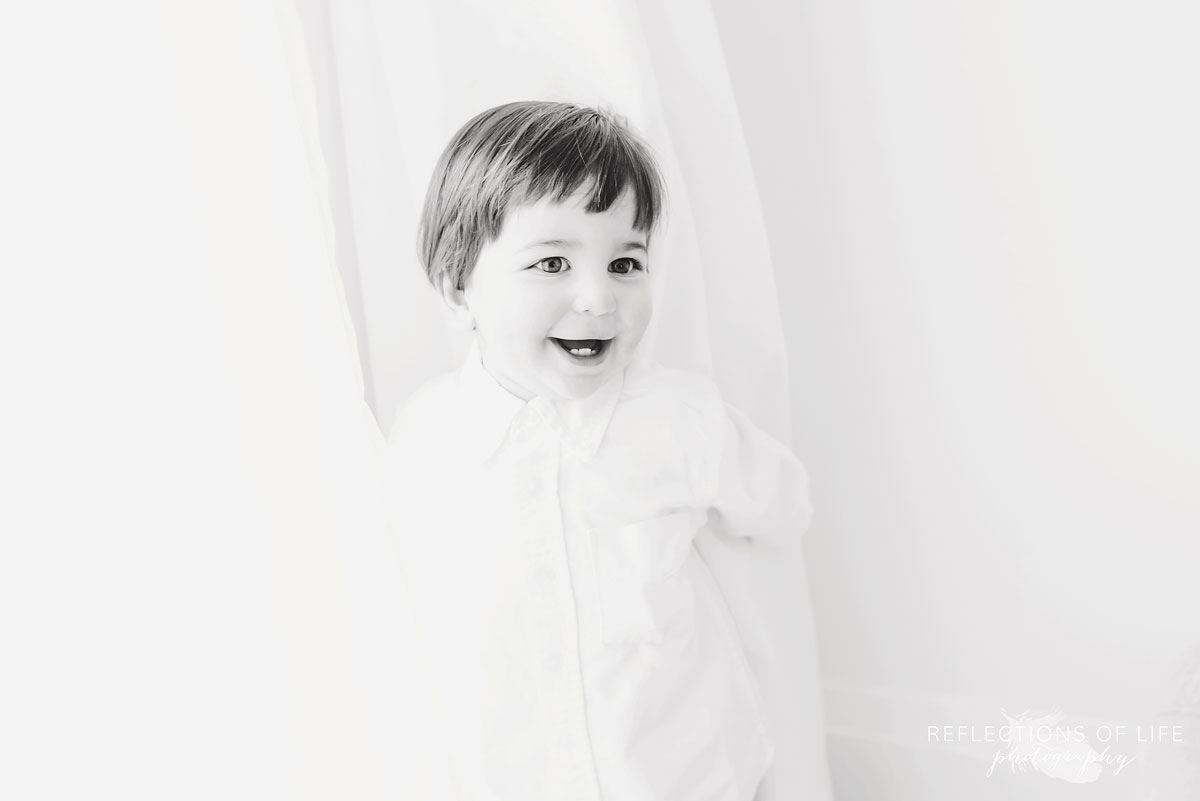 Little boy in white curtains