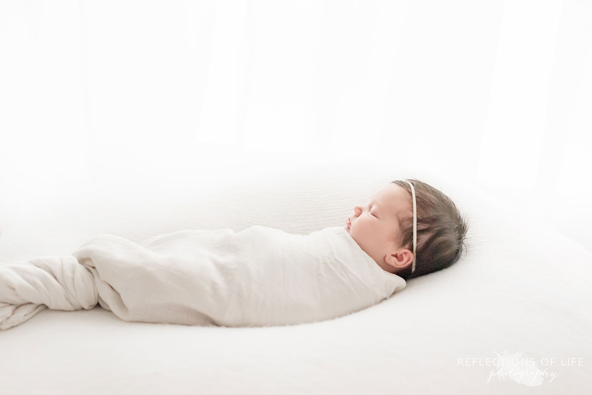 newborn baby girl swaddled in white on a white bed.jpg