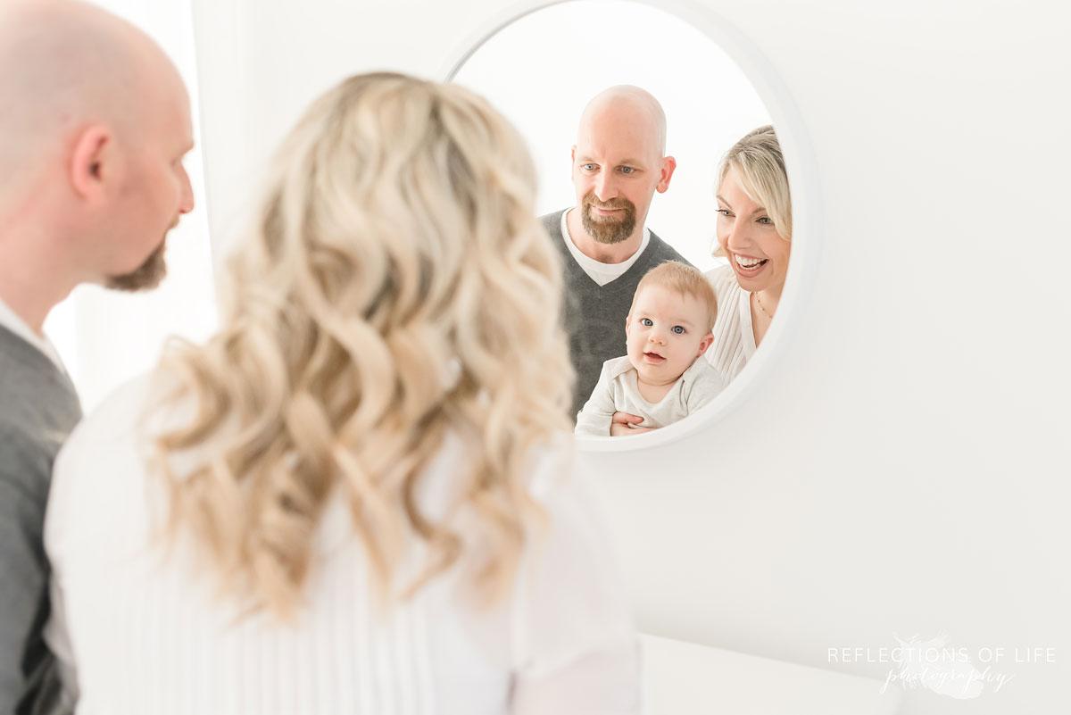 Copy of Copy of Baby boy looking into a mirror with his parents in Grimsby Ontario studio