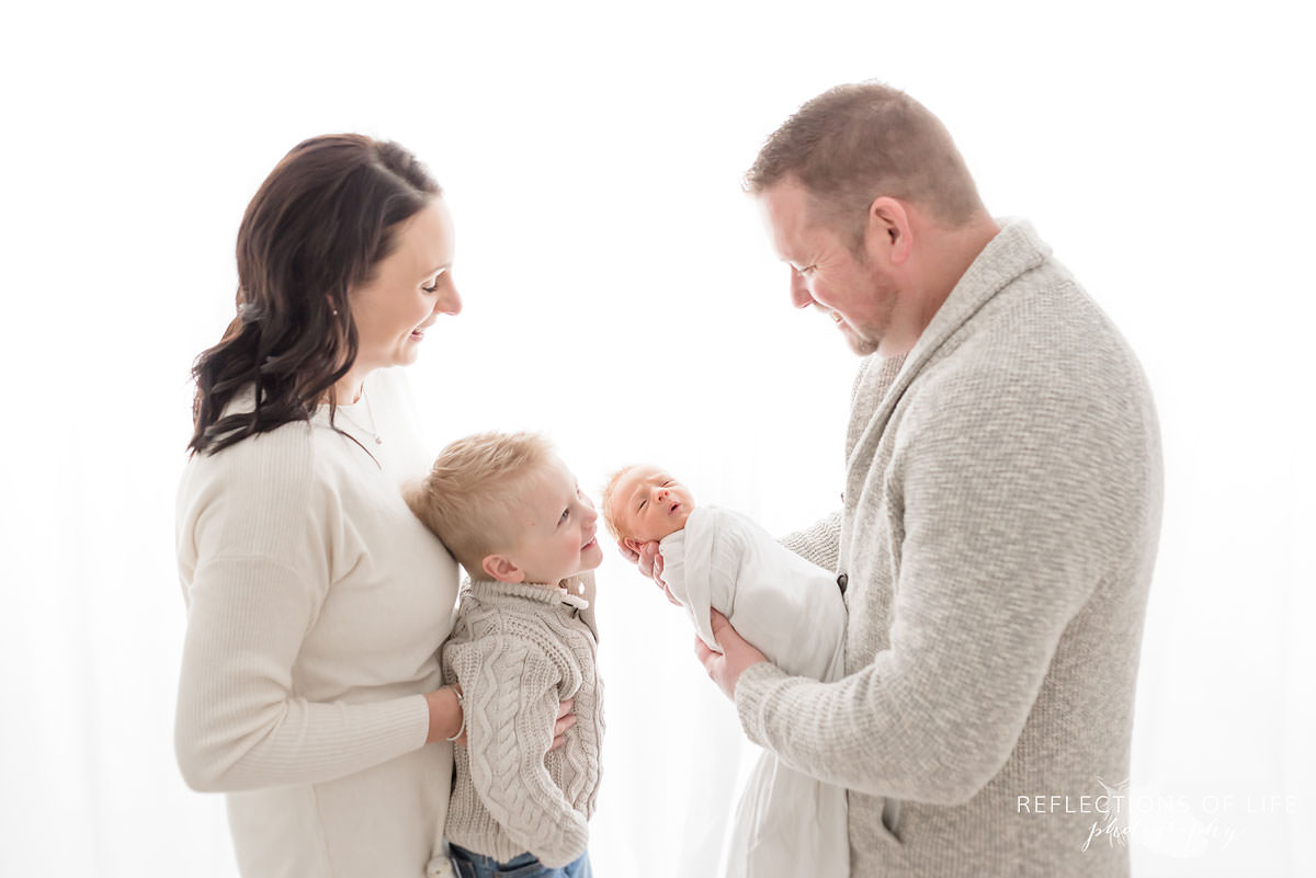 Portrait of Family holding newborn baby backlit.jpg