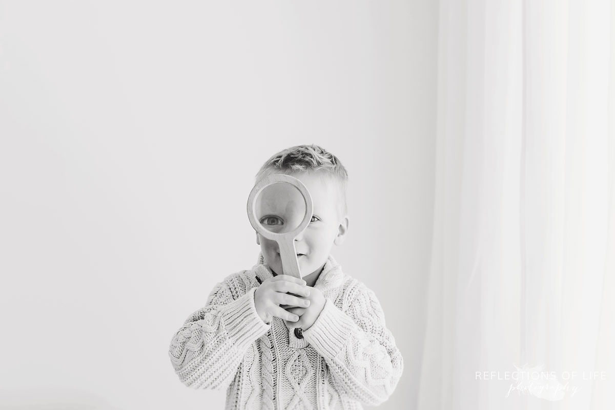 Little boy looking through a magnifying glass with a giant eye.jpg