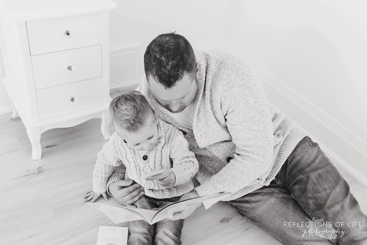 Son and daddy reading books on the studio floor in Grimsby Ontario studio.jpg
