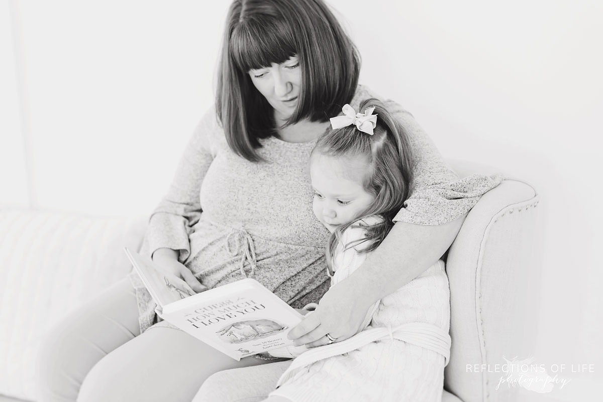 Mother and daughter read a book together in black and white