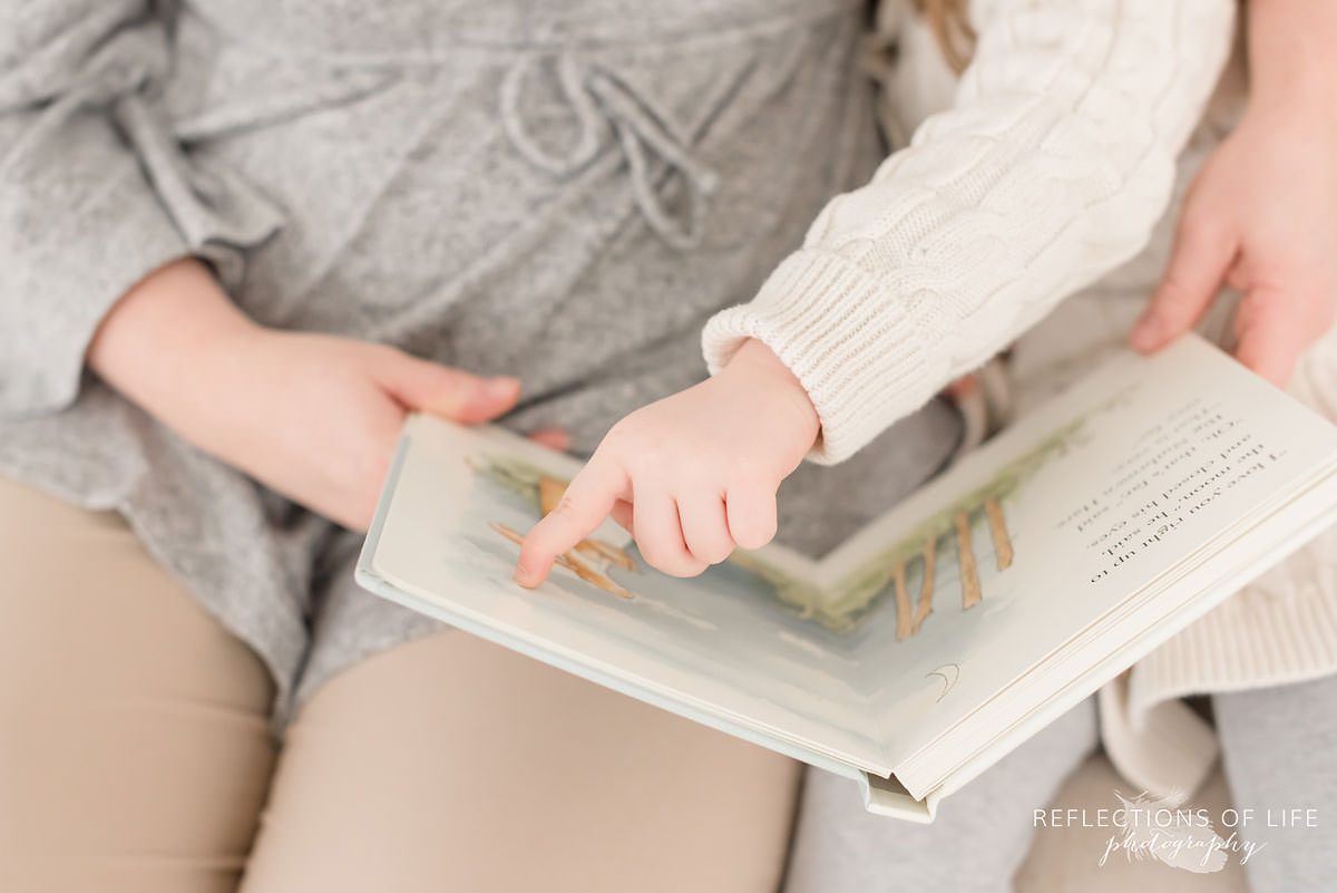 Daughter points out something in a book that mother is reading to her in Grimsby