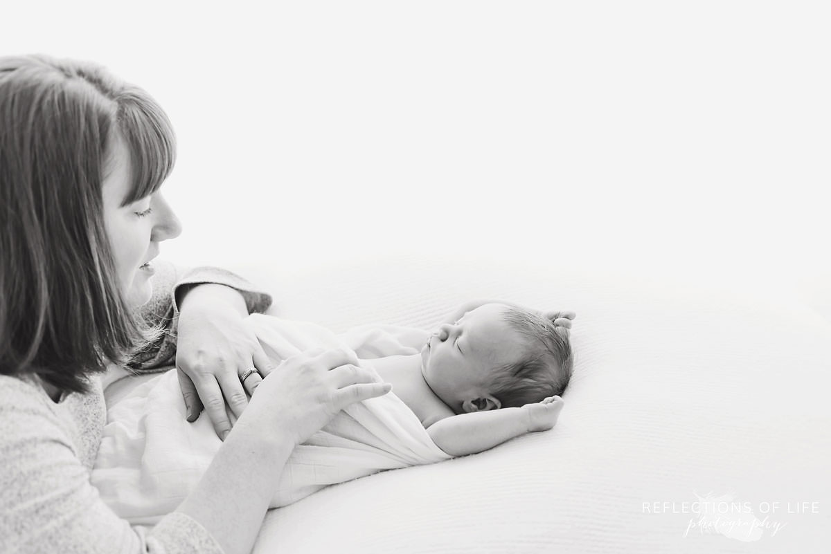 Mother lays on baby as they wake up in black and white