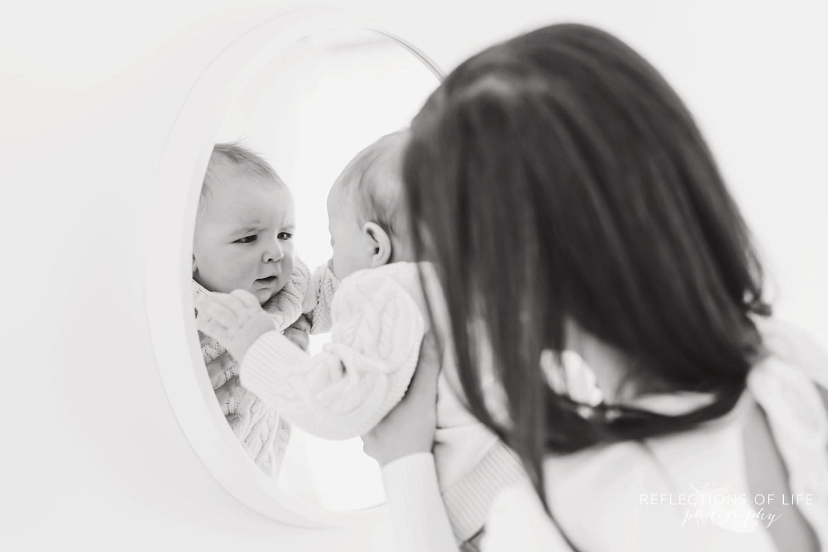 baby looks at himself in natural light studio in black and white