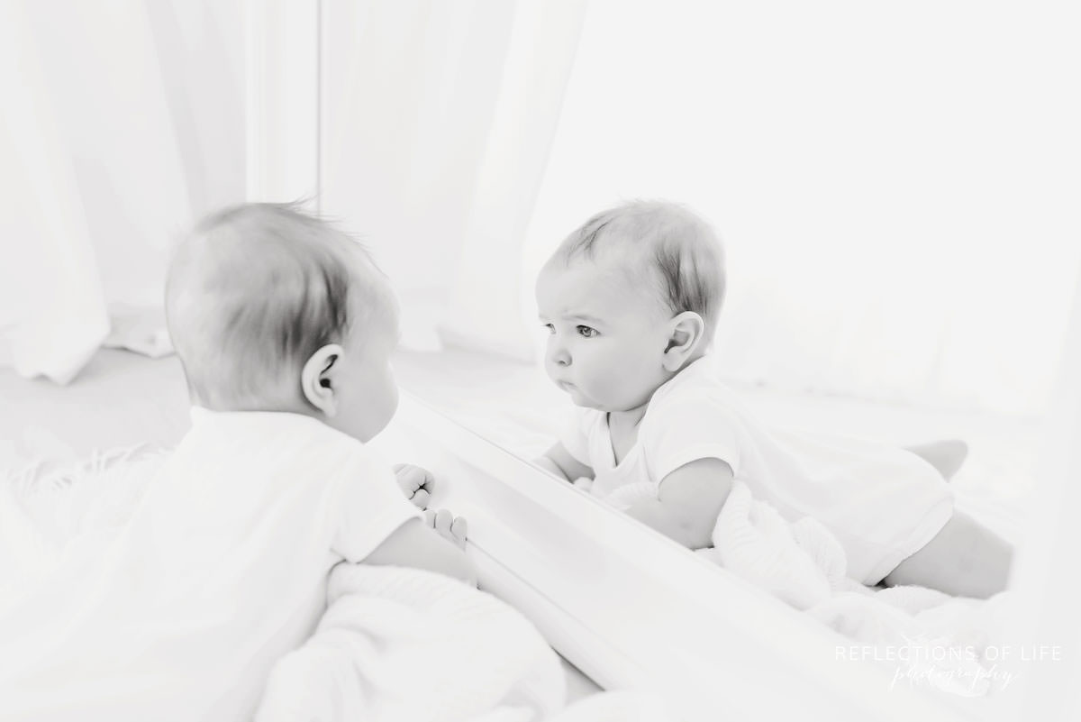 baby looks at himself in mirror in black and white