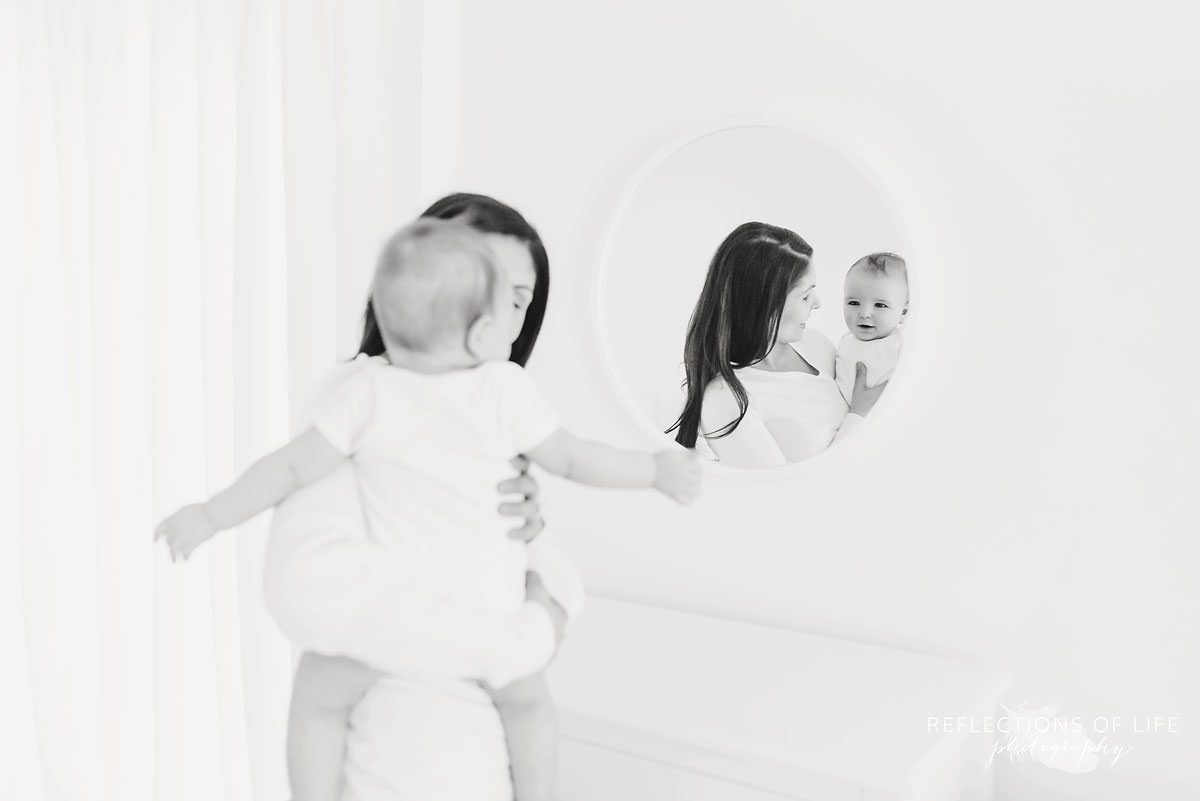 mother looks at baby as he looks at the mirror in black and white