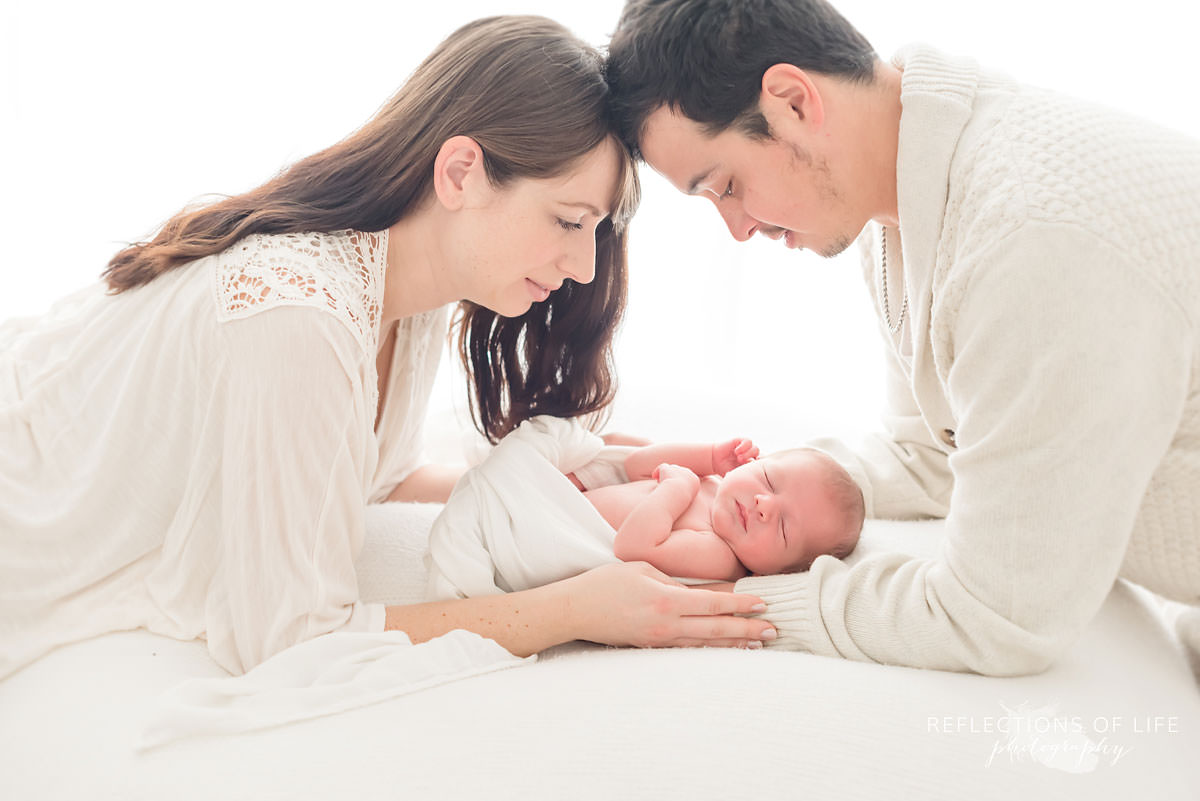parents watch over their baby while it sleeps in natural light studio