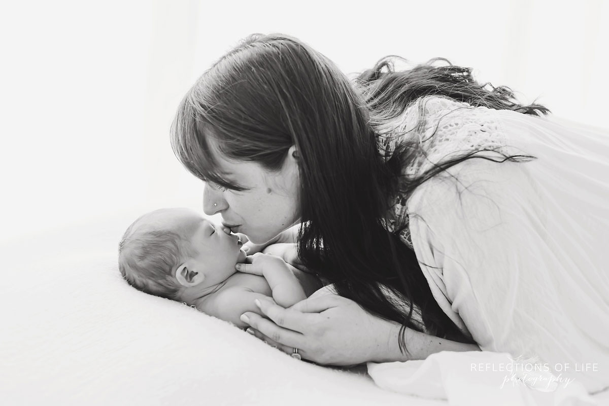 mother kisses her baby as he sleeps in black and white