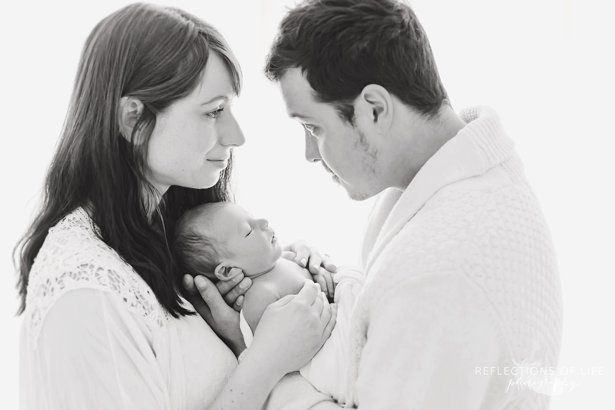 family of three hold their baby in black and white