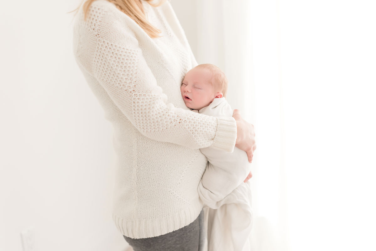 Mother holds her son to her stomach in natural light studio