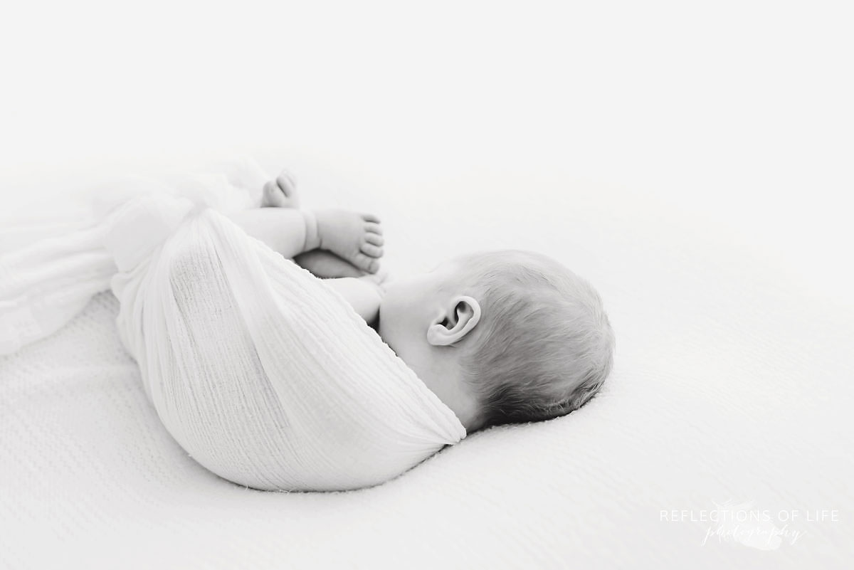 Baby sleeps swaddled facing the other way in black and white
