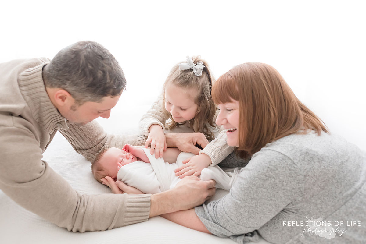 Jennifer Grebenc, Newborn Photography Niagara, Family of four watches over sleeping baby in natural light studio.jpg