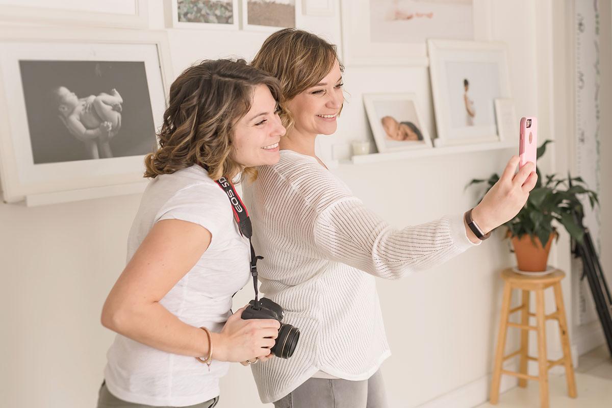 kayla and karen take a selfie in a natural light studio