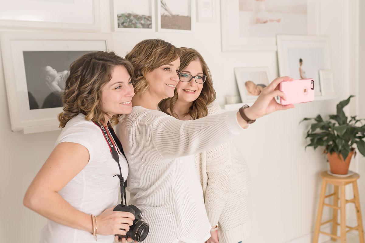 three newborn photographers share a selfie