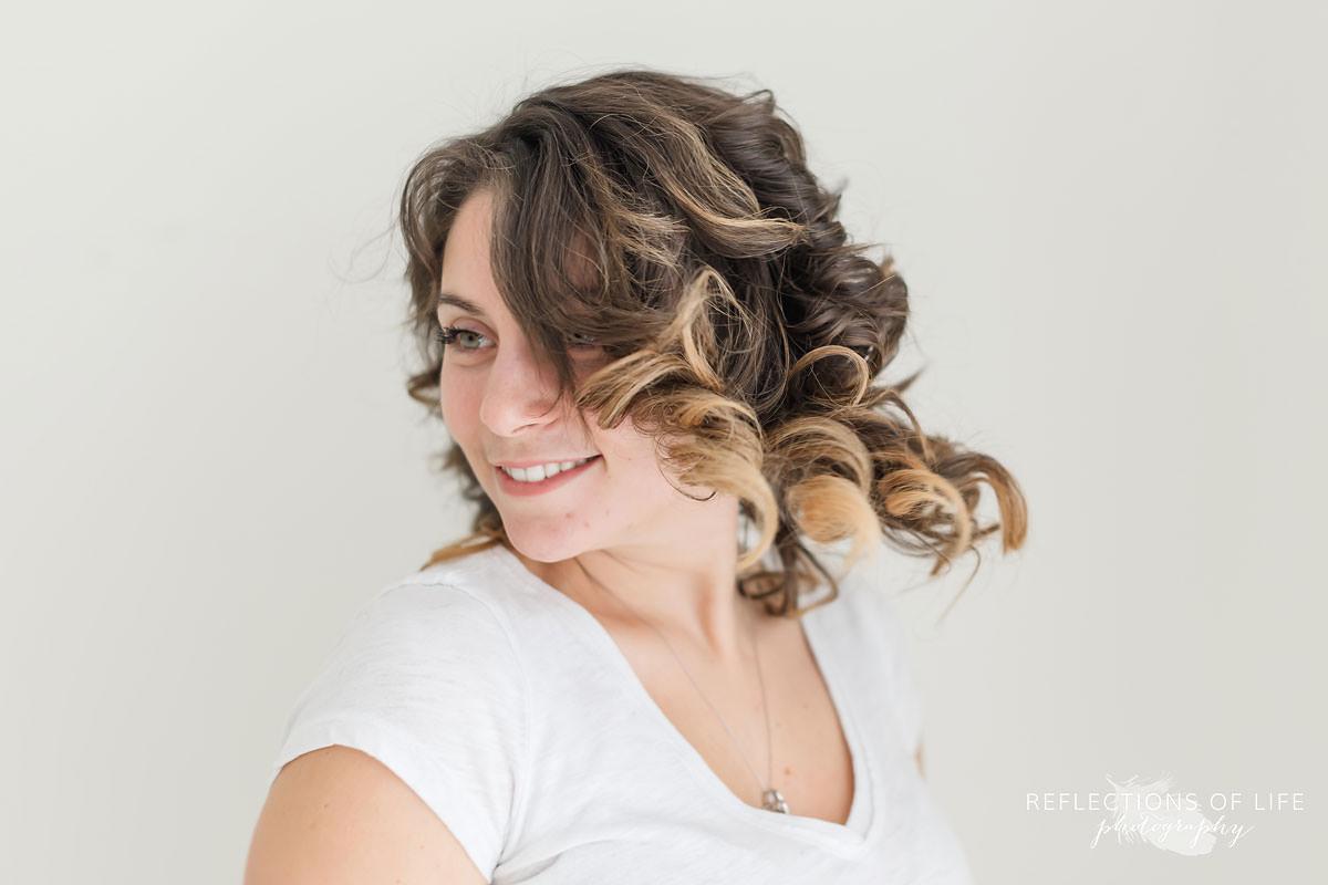 newborn photographer kayla flips her hair in natural light studio