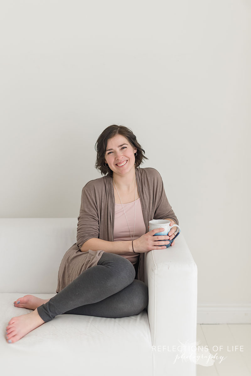 pretty lady sits comfy on the couch with her tea