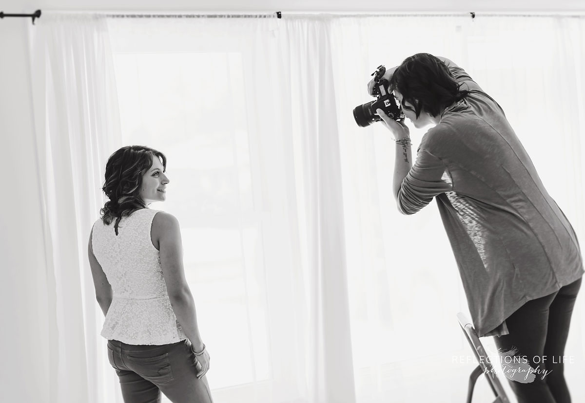 behind the scenes of photographer standing on ladder to photograph kayla