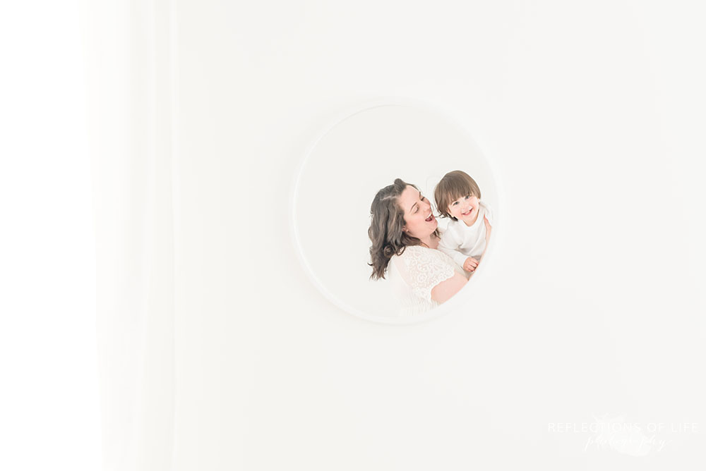 Natural light photography of mom and baby in mirror