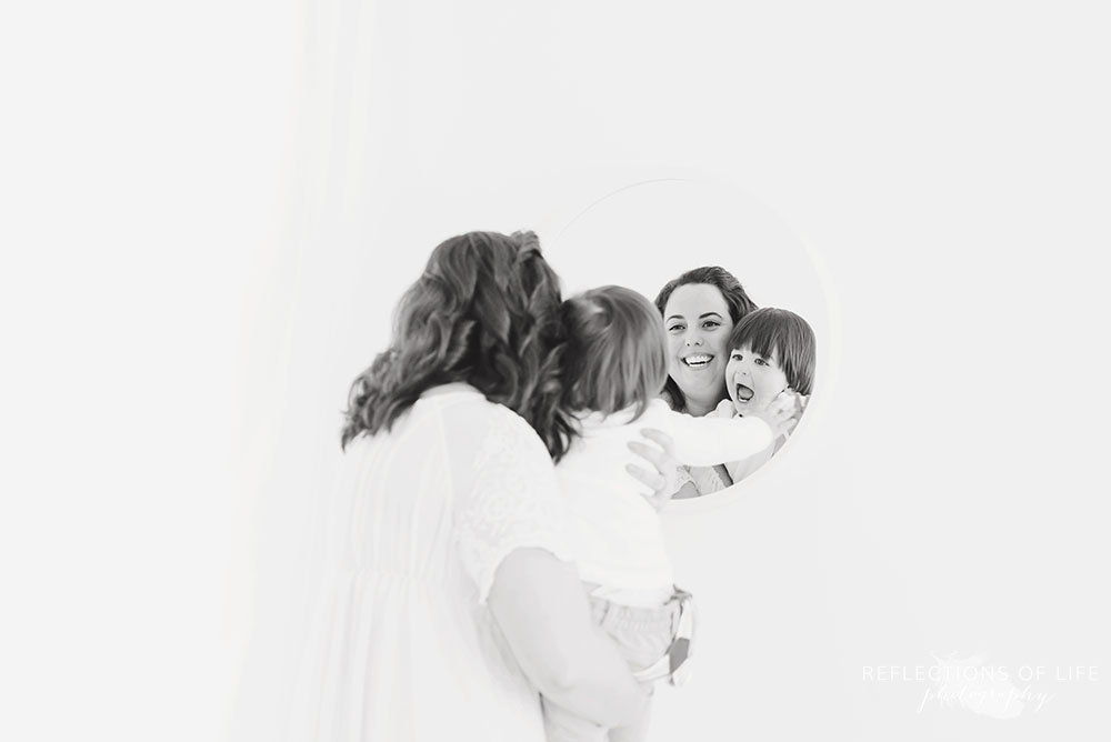 Baby and mom laugh while looking at reflection in the mirror