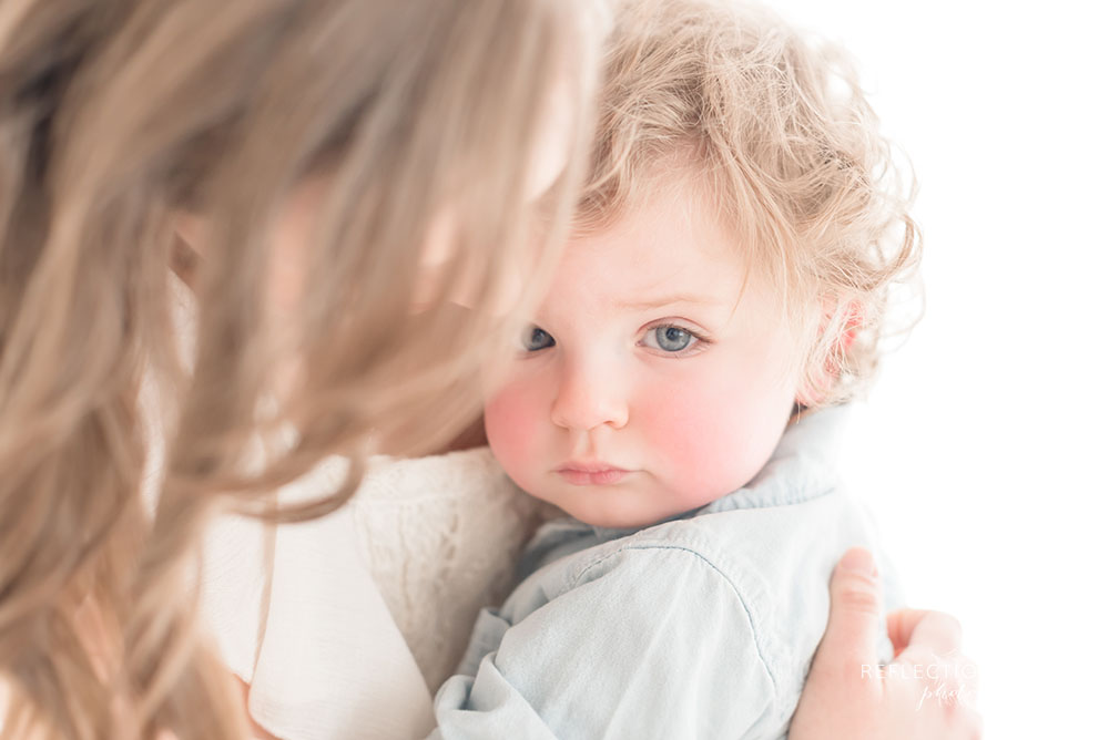 adorable little boy looks at the camera will mothers hair cover some of his face