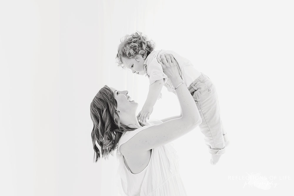 mama holds her baby up in the air in black and white in grimsby