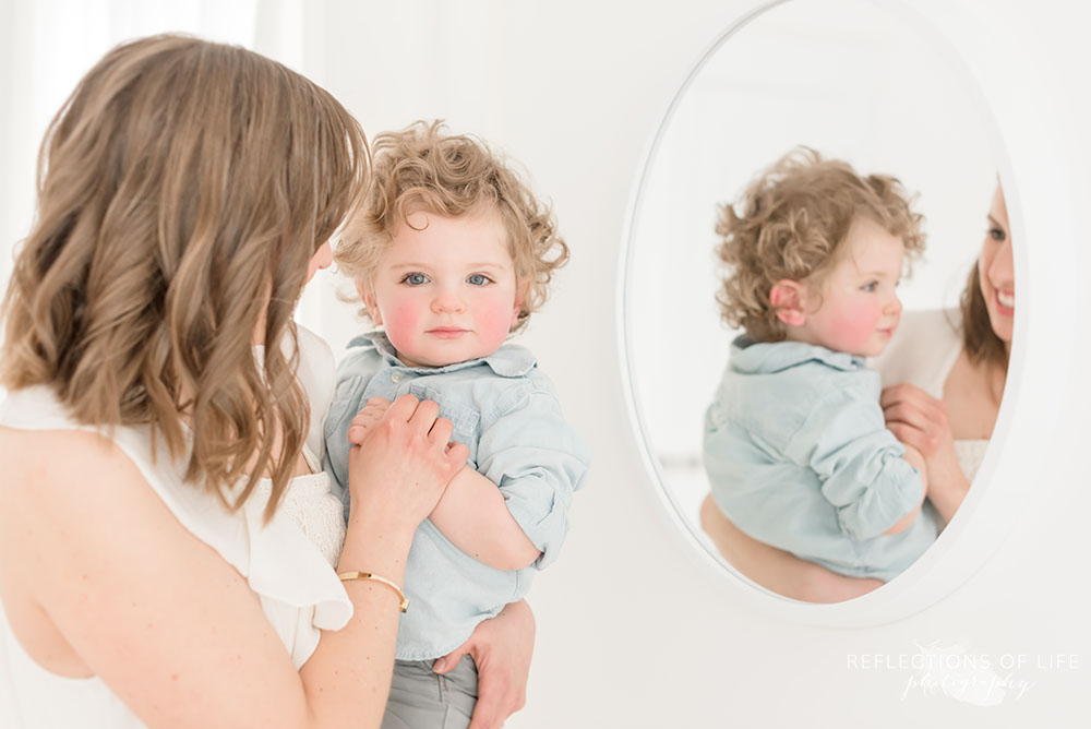mother and son pose for the camera with a mirror reflection of cute little boy