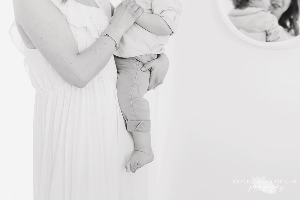 mama supports her boy in black and white in natural light studio