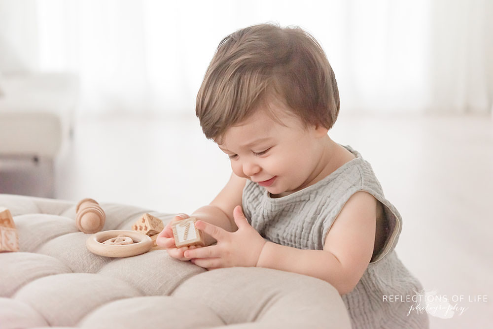 cute little boy smiles to himself while playing in natural light studio