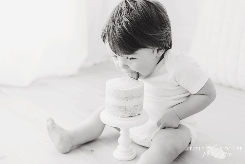 little boy licks the top of the cake in black and white