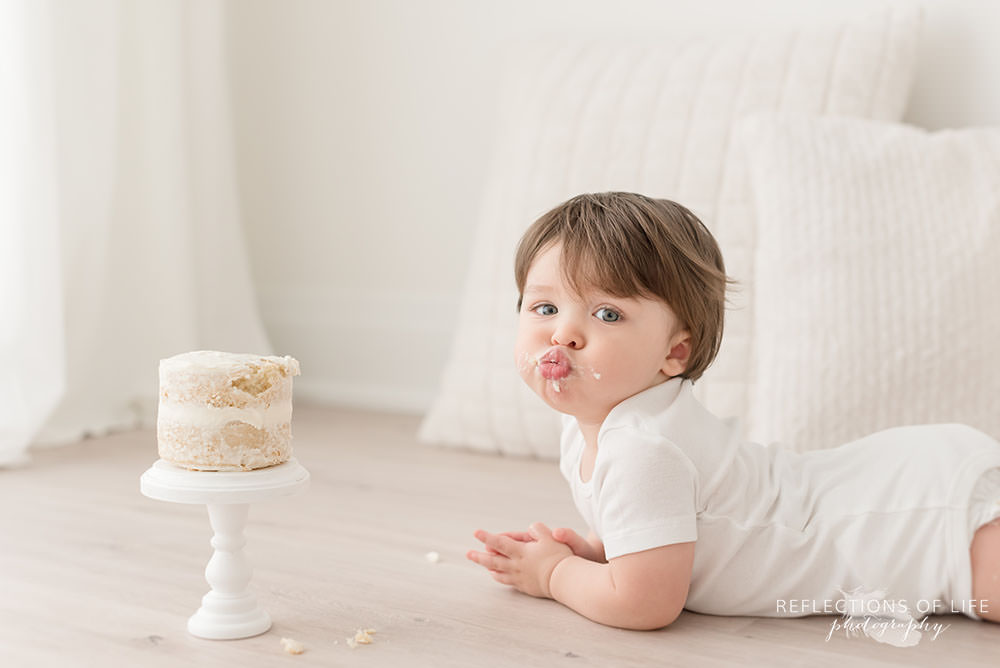 cute little boy gives cute kissy face at camera while lying down with his cake