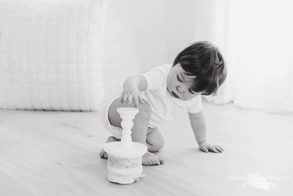 baby flips cake over in black and white