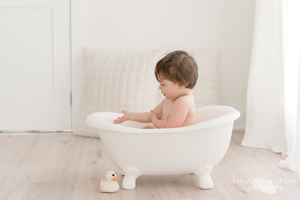 toddler looks at his hand while having a bath in natural light studio