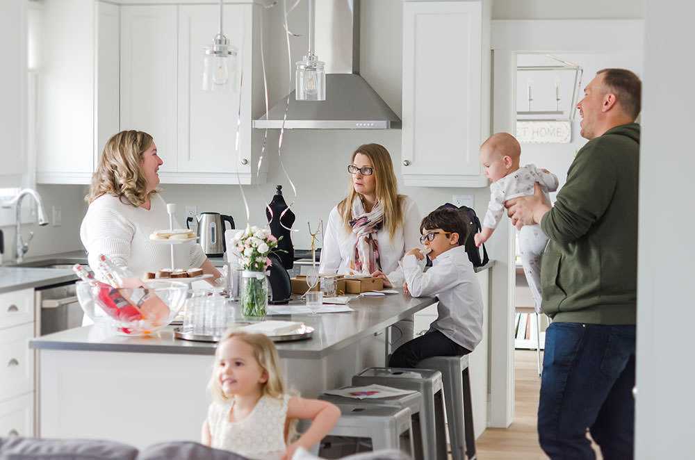 people socialize in the kitchen at the motherhood event