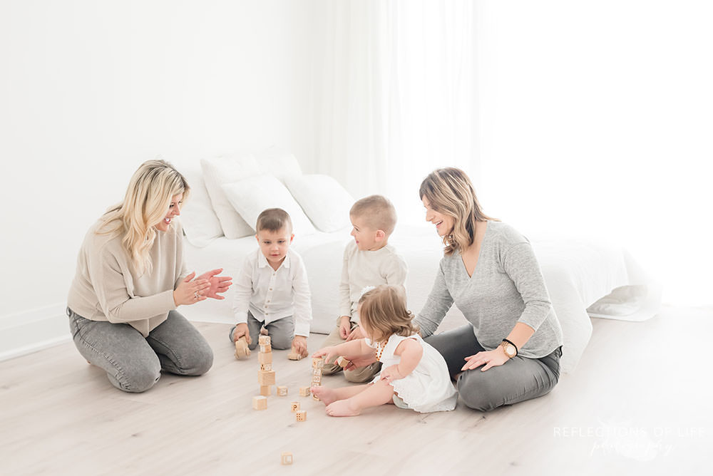 family of five play with blocks on the ground of natural light studio