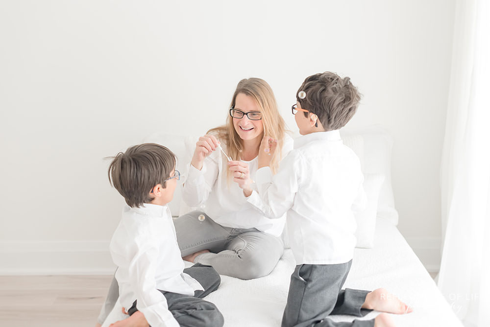mama with her two boys play with bubbles in natural light studio