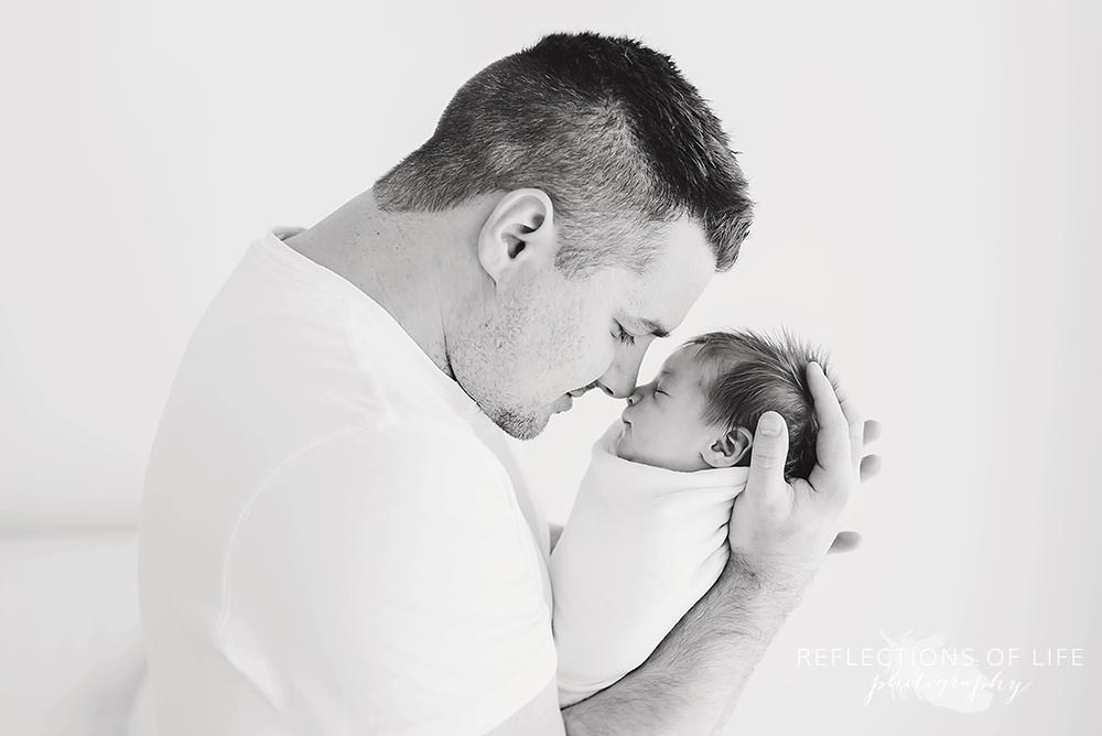 father and baby touch noses in black and white