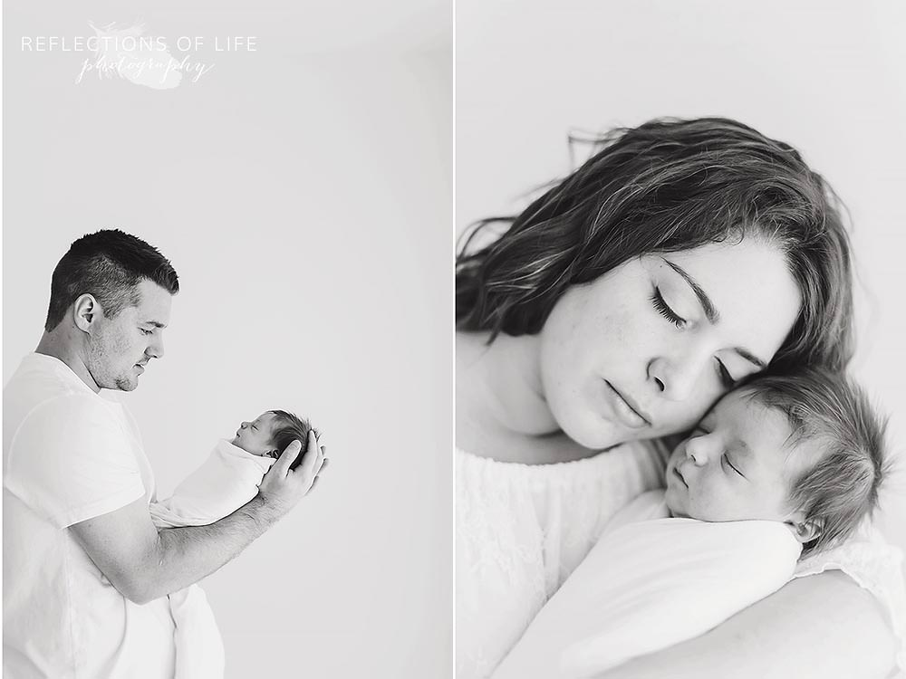 father and baby and mother and baby have special moments of affection in black and white