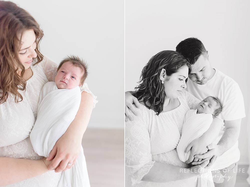 mama holds her baby and dad joins as well in black and white