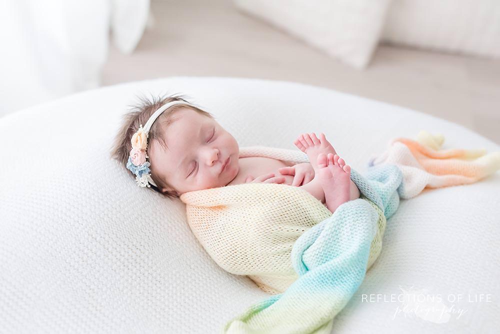baby sleeps in rainbow scarf