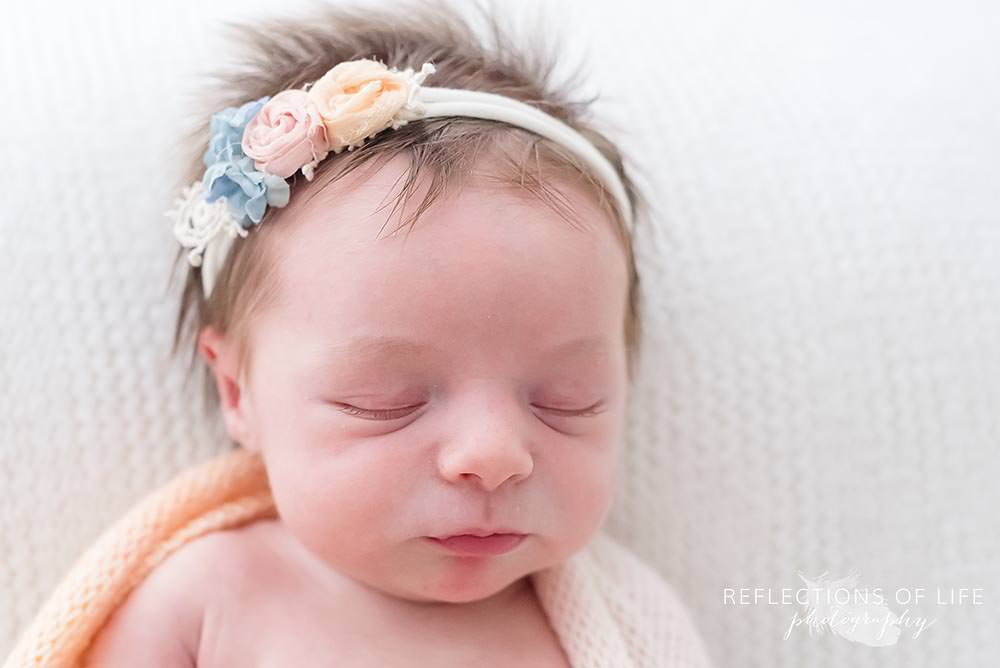 close up of baby sleeping with headband on
