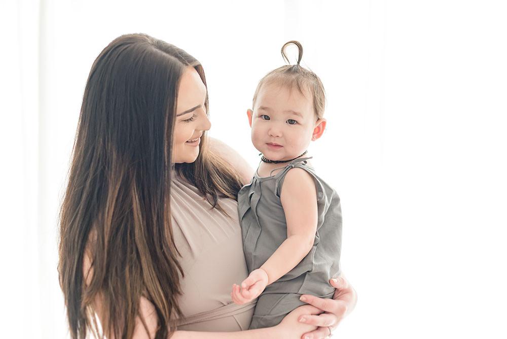 mama holds her little girl in natural light studio