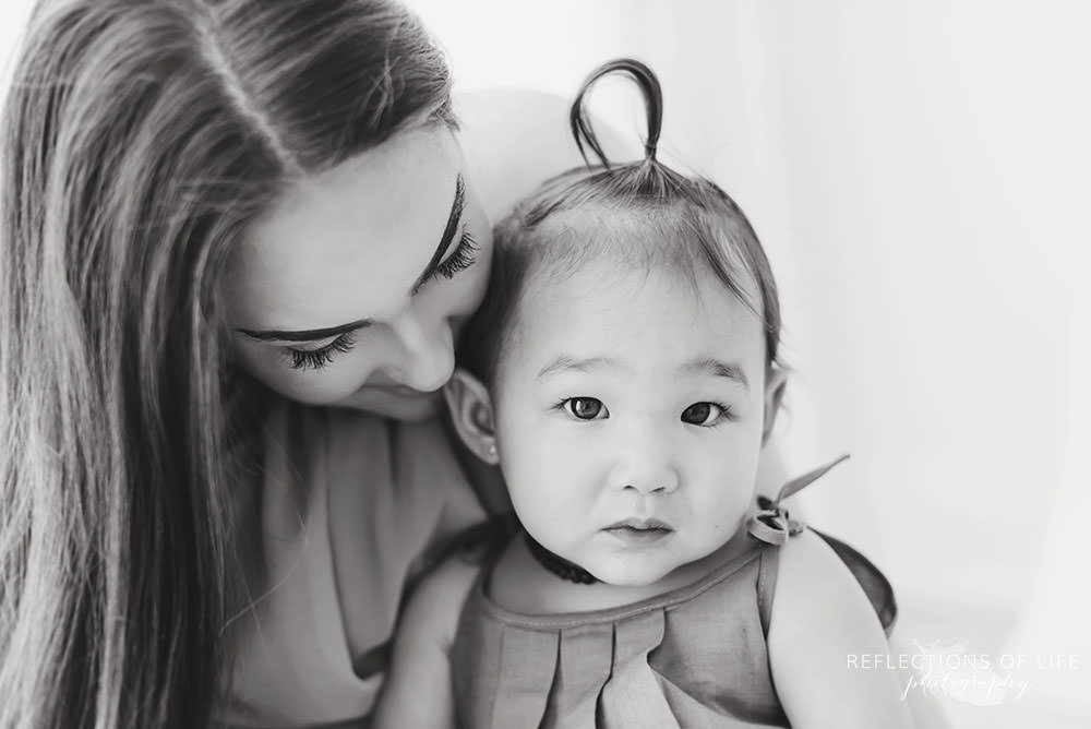 little girl looks at the camera with her mama in black and white