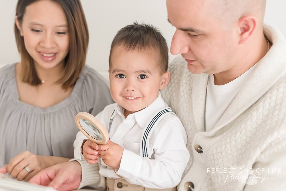 family of three in natural light studio with little boy smiling at the camera