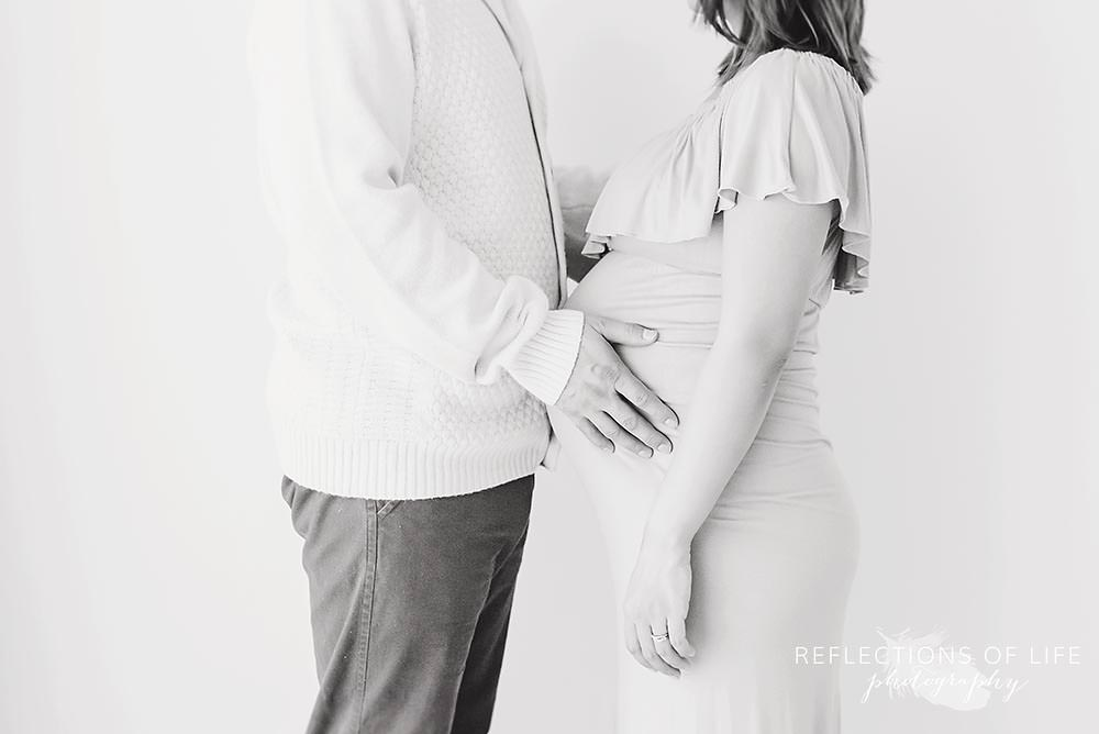 dad holds his wifes stomach in black and white