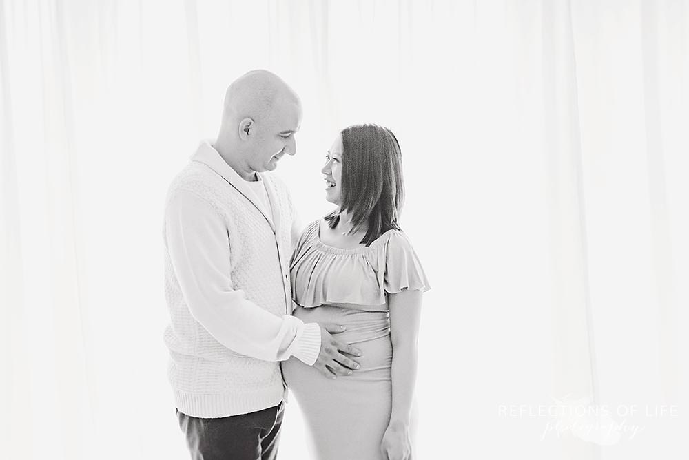 mama and dad smile at eachother as he holds her stomach in black and white